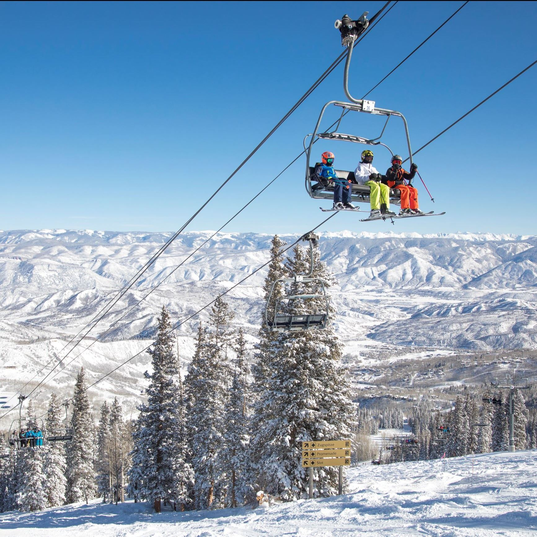 skiers riding ski lift
