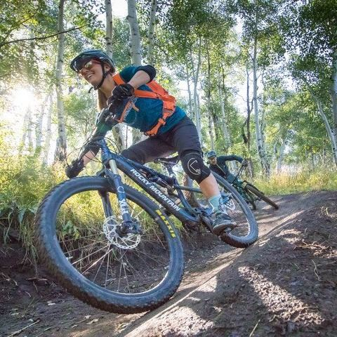 Woman mountain biking down hill with full gear on, smiling